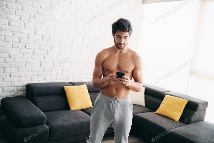 Man Working Out At Home With App On Mobile Phone