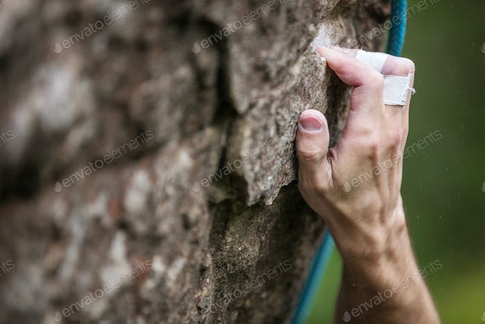 Rock climber's hand gripping hold on cliff