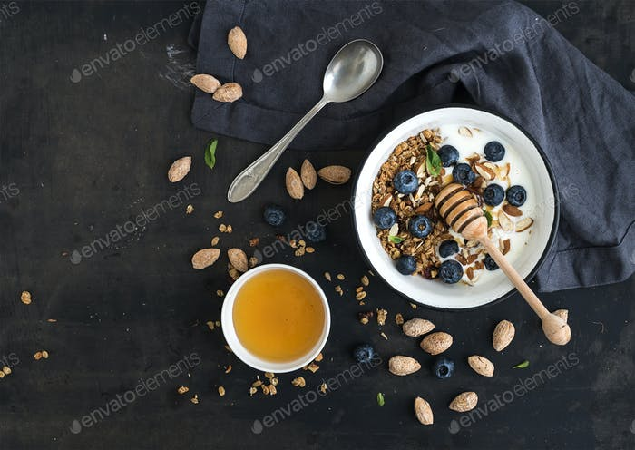 Healthy breakfast. Oat granola with fresh blueberries, almond, yogurt and mint