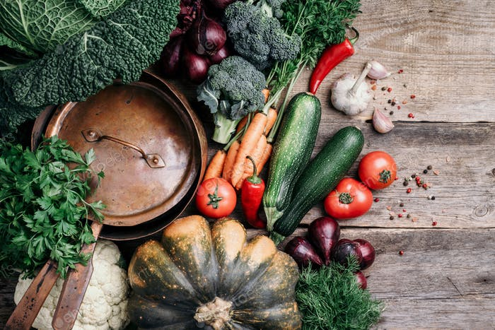 Healthy, clean food cooking and eating concept. Copper pan, colorful autumn vegetables on wooden