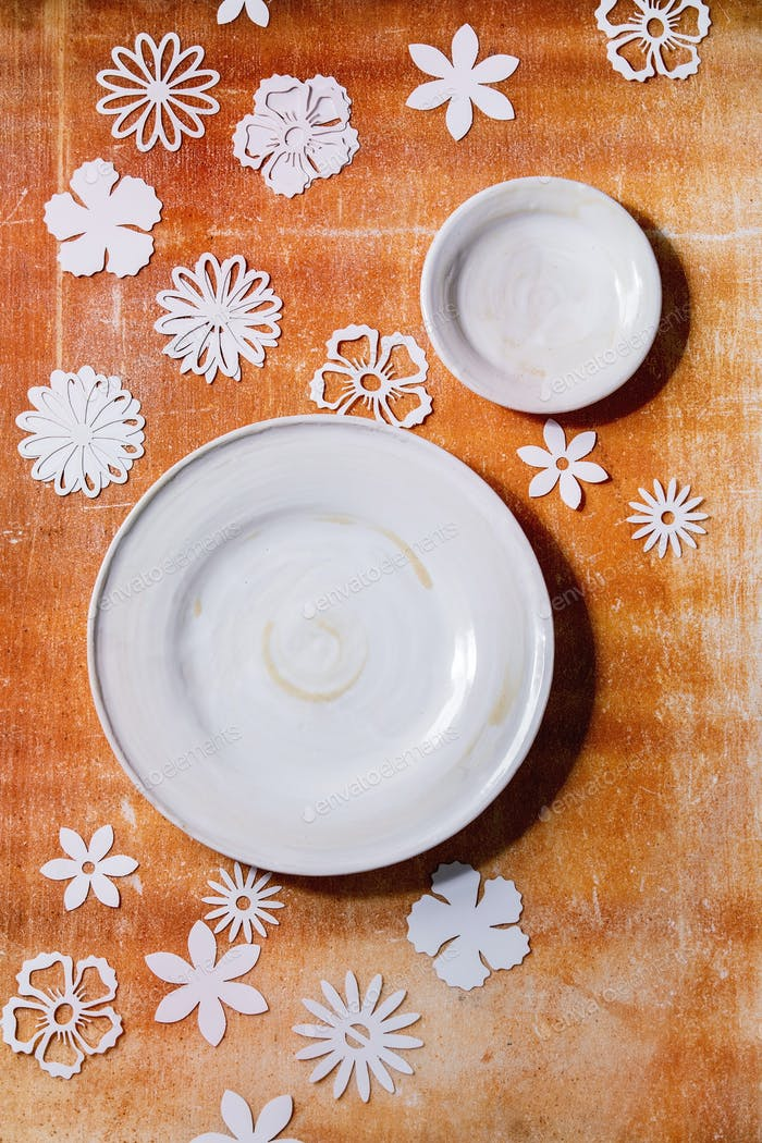 Empty white plates with paper flowers around