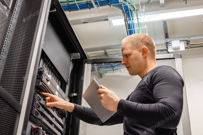 Male IT Technician Holding Digital Tablet Analyzing Servers in Datacenter