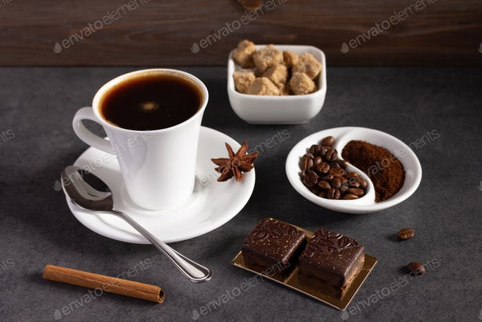 Cup of coffee and beans on table background. Set of coffee and sweets