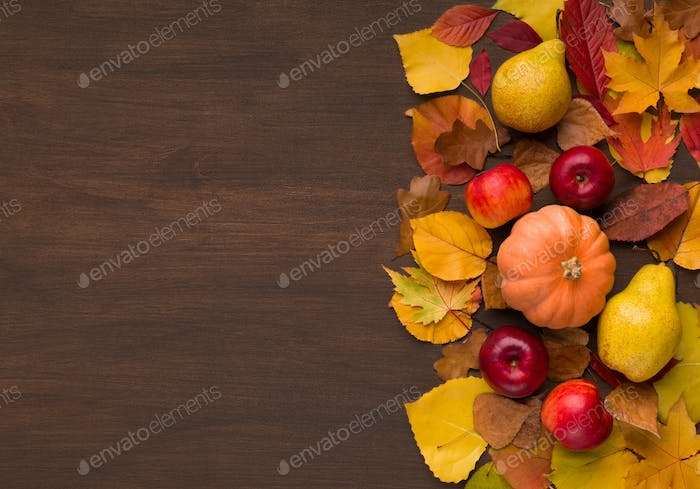 Autumn harvest of red apples and pumpkin on fallen leaves