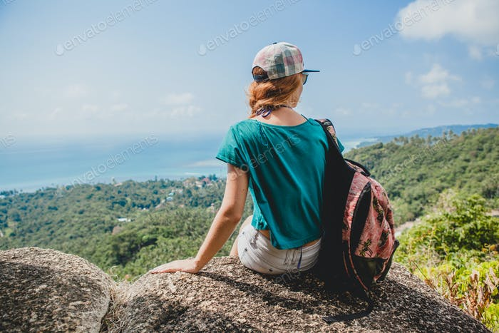 ginger woman traveling with backpack in mountains