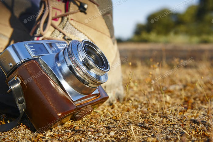 Vintage camera with hiking boots on the ground. Travel background