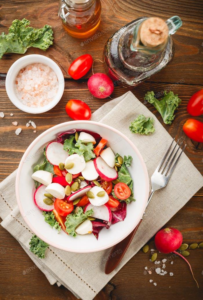 Salad with cherry tomatoes, radsh and mozzarella, lettuce mix
