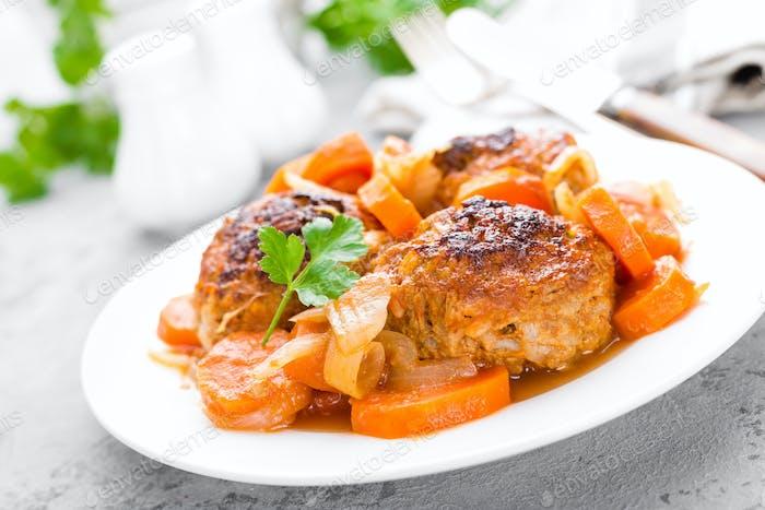 Fischfleischbällchen oder Noisettes gebacken mit Karotte, Zwiebel und Tomatensauce. Fischfleischbällchen auf Teller