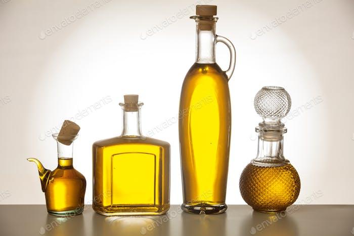 Set von Flaschen mit Olivenöl auf Farbverlauf Hintergrund