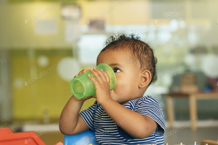 Happy baby drinking water and playing.