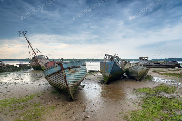 Abandoned fishing boats under a brooding sky