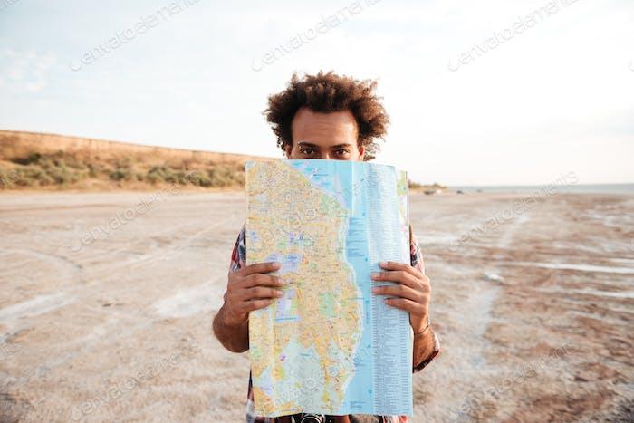 Verspielter Mann stehend und versteckt hinter der Karte im freien