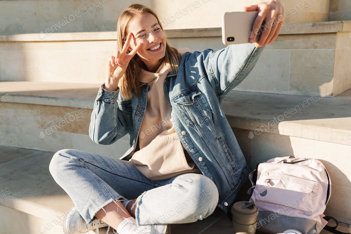 Cheerful young blonde girl taking a selfie with mobile phone