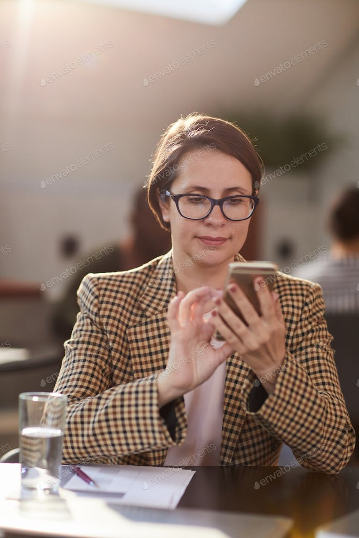 Business Woman Using Smartphone in Cafe