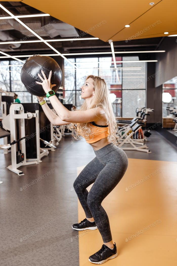 Slender blond girl with long hair dressed in a sportswear is doing back squats with heavy fitness
