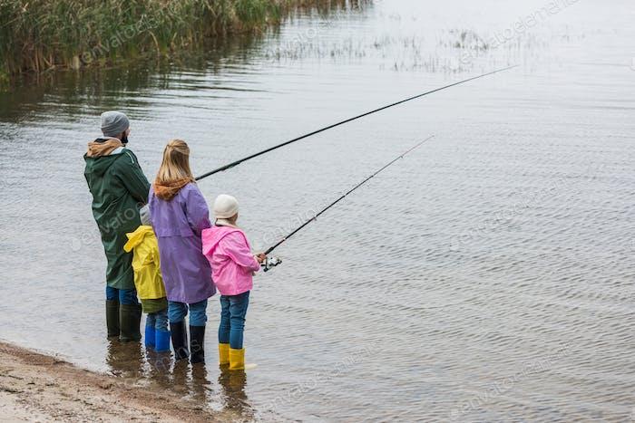 Familie in Regenmänteln und Gummistiefeln, die zusammen f