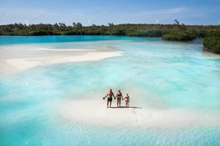 family on the tropical island of Mauritius.The family stands on a small island in the Indian Ocean