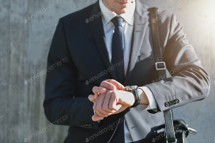 Stylish man wearing suit looks at watch