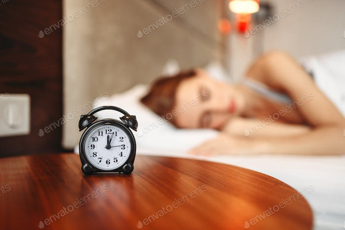 Alarm clock, woman covering her ears with pillow