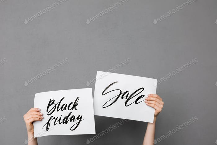 Close up photo of woman hands up that holding beautiful postcards on gray background