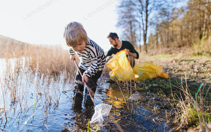Father with small son collecting rubbish outdoors in nature, plogging concept