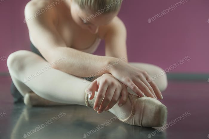 Ballerina sitting and bending forward in the ballet studio