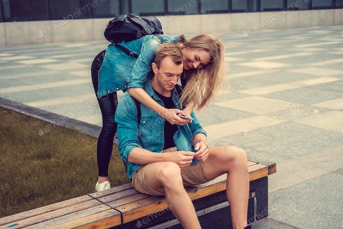 Привлекательная городская пара с помощью смартфона.