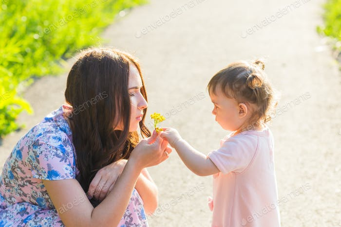 Baby daughter Giving Mother Flowers in the park
