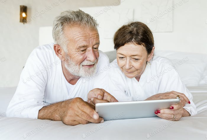 Senior couple using a tablet in bed
