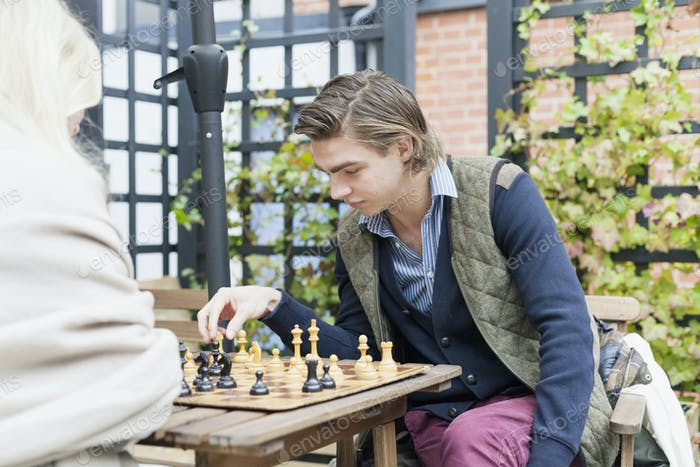 Young couple playing chess at cafe backyard