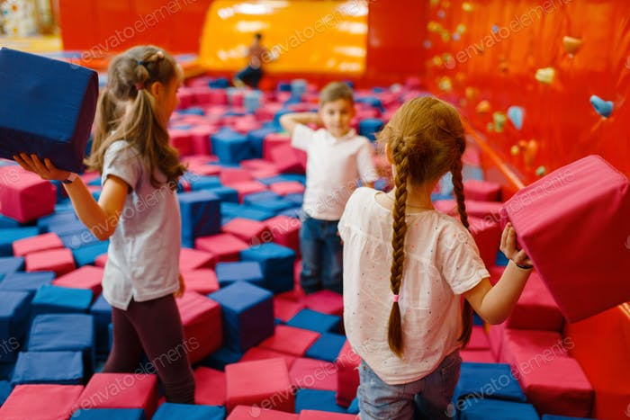 Jouful children plays among soft cubes, playground