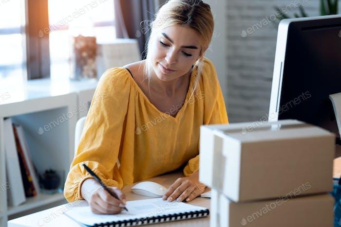 красивая внештатная деловая женщина продавец пишет новые идеи в блокноте