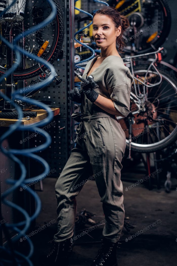 Diligent attractive woman is fixing bicycle at busy workshop in between pneumatic wires