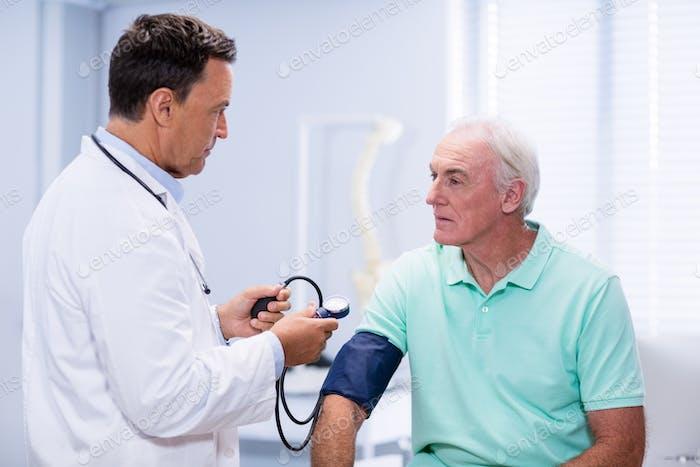 Arzt Blutdruck eines Patienten überprüfen