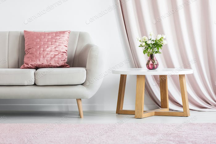 Pink pillow on beige sofa
