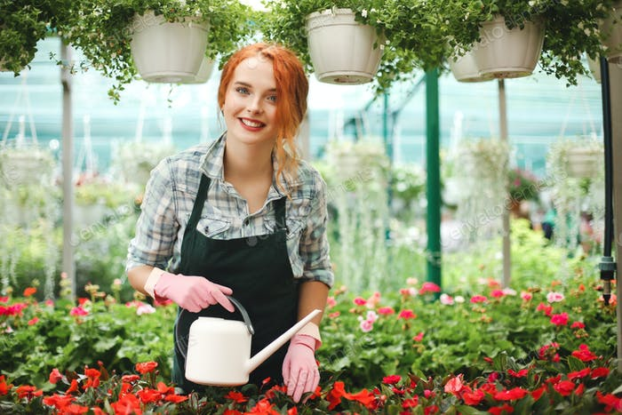 Young beautiful florist in apron standing with watering can and happily looking in camera