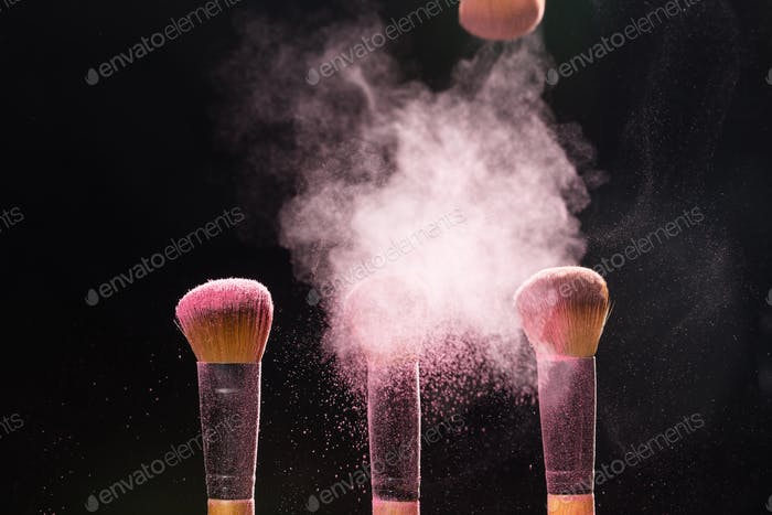 Mineral makeup and beauty concept - Makeup brushes in pink powder over dark background