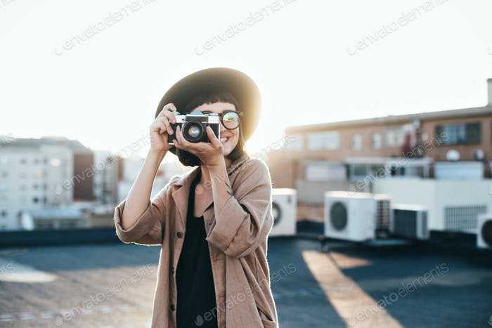 Hipster millennial woman at rooftop at sunset