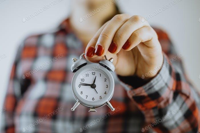 Zeit-Management. Kleiner Wecker in weiblichen Händen