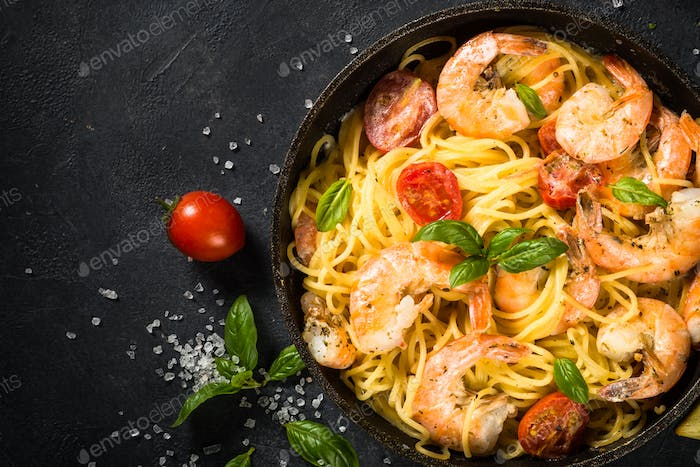 Pasta seafood with shrimp on black table