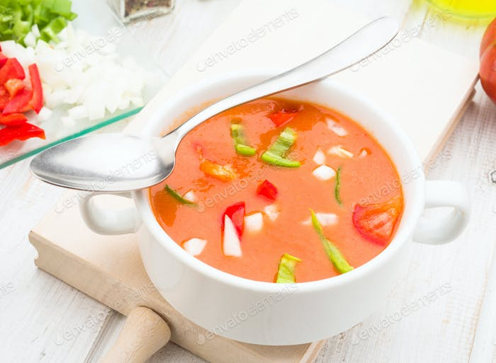 gazpacho soup with spoon in white china bowl