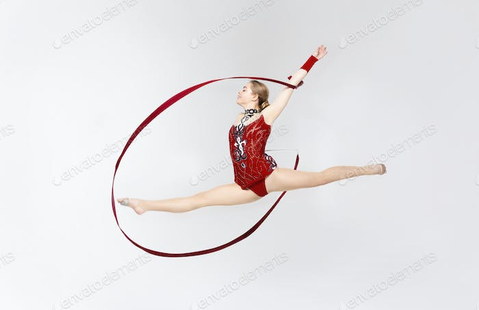 Charming gymnast with string doing split leap in the air on white background