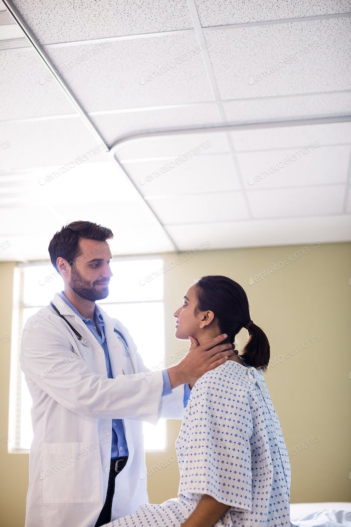 Doctor examining patients neck in hospital