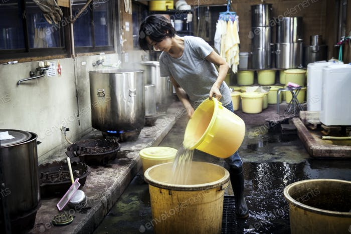 Japanese woman working in a textile plant dye workshop, pouring hot water into yellow plastic