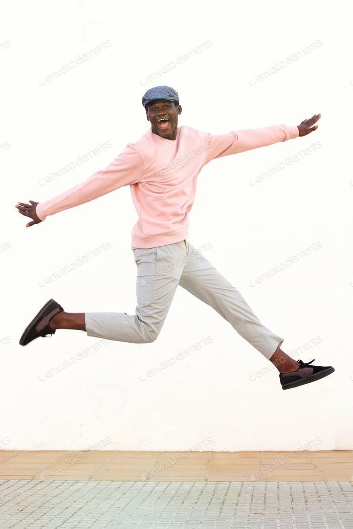 Excited young african man jumping with joy against white wall
