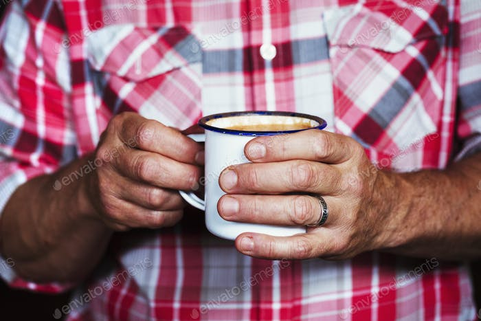 Specialist coffee shop. A man holding a cup of coffee.