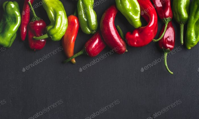Colorful hot chili peppers on black wooden background, copy space
