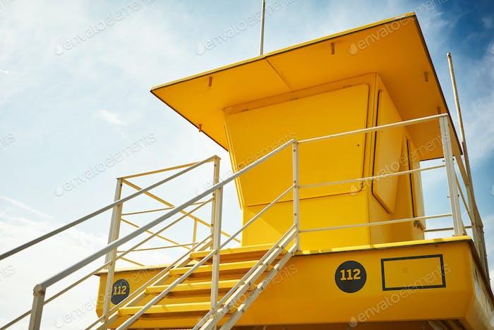 Yellow lifeguard post on an empty beach