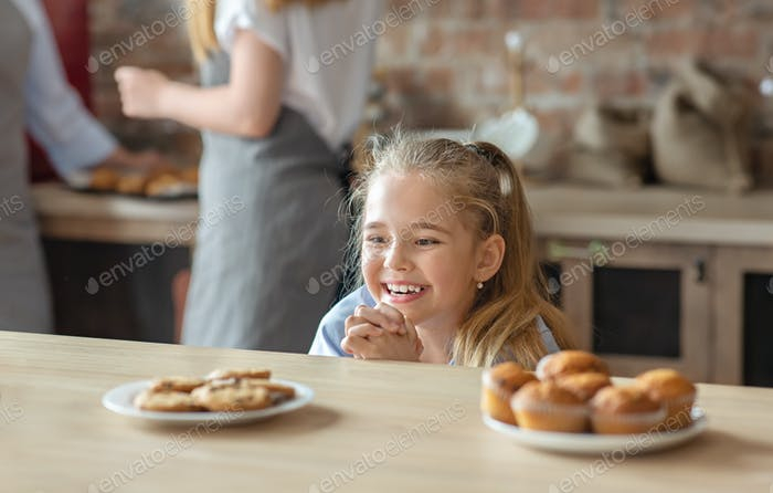 Adorable little girl looking with desire at sweets