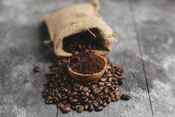 coffee beans in wood saucer and bag with grunge black background